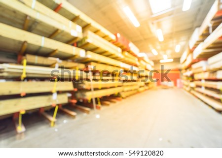 Blurred stack of new wooden bars on shelves inside lumber yard of large hardware store in America. Rack of fresh mill/cut wood timber in warehouse. Industrial wood texture and construction background.