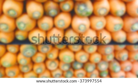 Blurred stacked carrots at a supermarket - stock photo