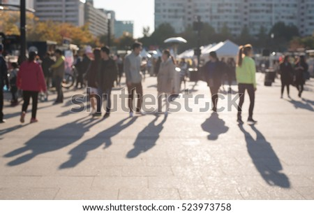 Blurred street people in Korea, perspective people walking in late afternoon with long shadow, walkway in the park, defocused image use for background