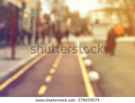 Blurred street with bike line, people and blurred lights. Blurred street background / texture. - stock photo
