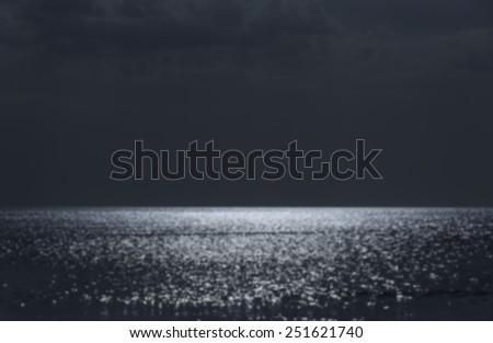 Blurred sunlight shining reflection on sea water surface. - stock photo