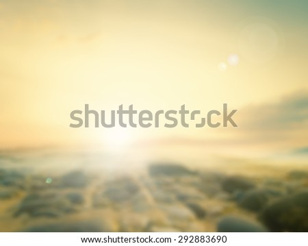 Blurred sunset background. Sandy beach backdrop with turquoise water and bright sun light. Summer holidays concept. - stock photo