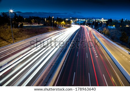 Blurred Tail Lights And Traffic Lights On Motorway - stock photo