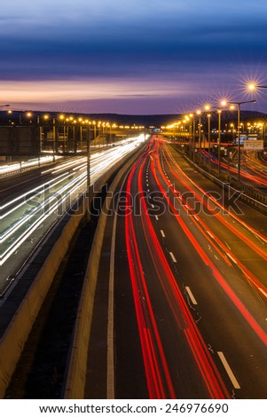 Blurred tail tights and traffic tights on motorway with a long exposure photograph at night - stock photo