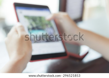 blurred the background of multitasking man using tablet or smart in coffee shop