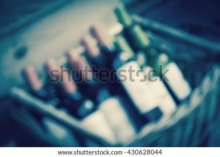 Blurred toned photo wine bottles in wicker wooden box.  - stock photo
