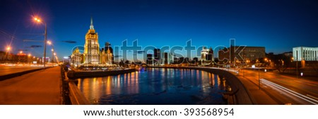 Blurred travel backgrounds - aerial view of Hotel Ukraina with river and skyscrapers in Moscow, Russia. Sunset over Kutuzovsky Prospect. Clear blue sky - stock photo