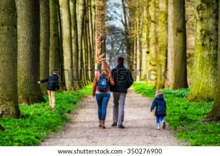 Blurred travel backgrounds - family walking down the pathway at beautiful garden of De Haar Castle in Utrecht, Netherlands in spring - stock photo