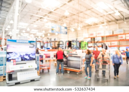 Blurred TVs shopping large wholesale club. Television retail shop, row of big screen, smart TVs display on shelves. Store staff help customers select and use flatbed cart carry TV to checkout counter.
