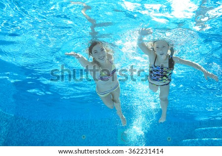 Blurred underwater: children swim in pool, happy active girls have fun under water, kids sport on family vacation  - stock photo