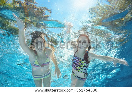 Blurred underwater: children swim in pool or sea, happy active girls have fun under water, kids sport on family vacation