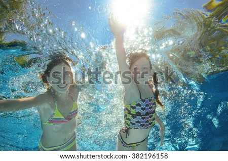 Blurred underwater: children swim in pool or sea, happy active girls have fun under water, kids sport on family vacation  - stock photo