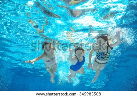 Blurred underwater: family swim in pool or sea, happy active mother and children have fun in water, kids sport on family vacation