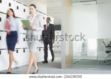 Blurred view of businesswomen walking in office - stock photo