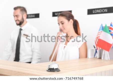 Blurred view of two hotel receptionists at workplace