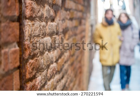 Blurred view of young couple walking on a narrow european street. perspective bricked wall on foreground. - stock photo