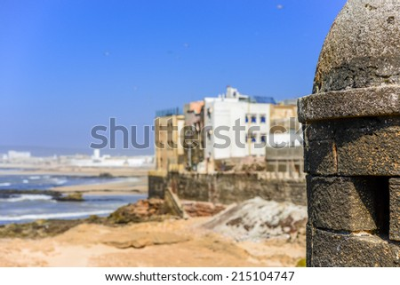 Blurred view to seaside and residential with a dark stone construction on the foreground