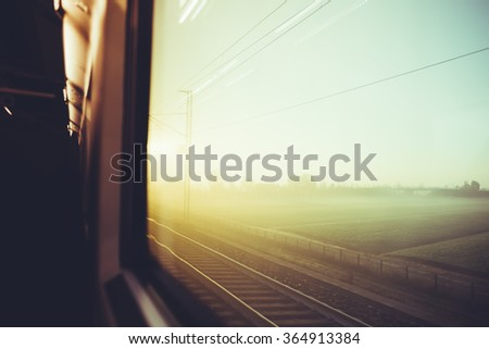 Blurred vintage filtered countryside view by a train window - travel, transport, journey concept - stock photo