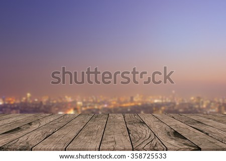 Blurred warm night city background with wood panels perspective.blur downtown skyline backdrop concept.blurry urban sunset/sunrise hours wallpaper with wood tiles stripe floorboard for montage display