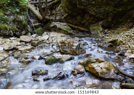 Blurred water in motion among rocks in a river. Slovak Paradise, Slovensky Raj National Park, Slovakia
