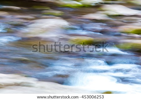 Blurred water in mountain river. Natural abstract background, defocused with  panning motion.