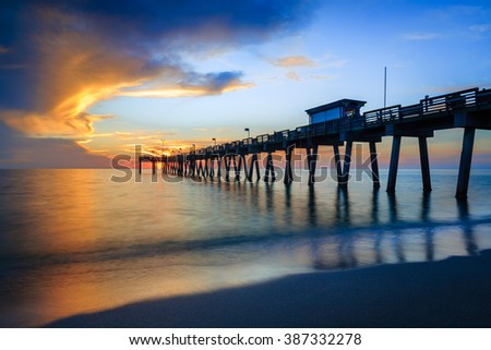 Blurred water softens as the sun sets over Venice Pier in Florida - stock photo