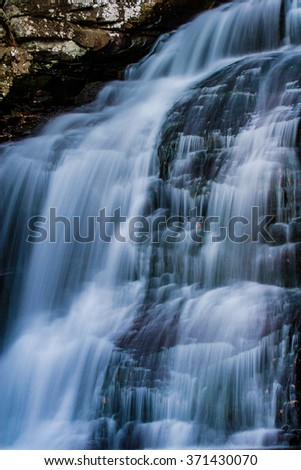 Blurred water streams down a waterfall in a long exposure shot - stock photo