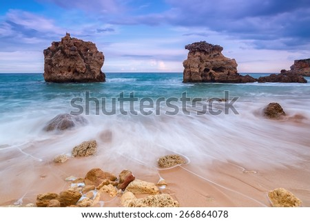 Blurred waves flow down along the rocky shore. Beautiful landscape before the storm. - stock photo