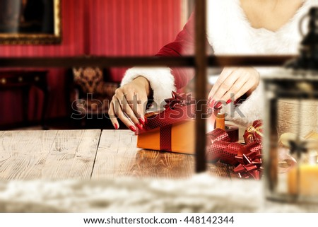 blurred window sill with snow and lamp with red ribbon and woman hands and box of gift