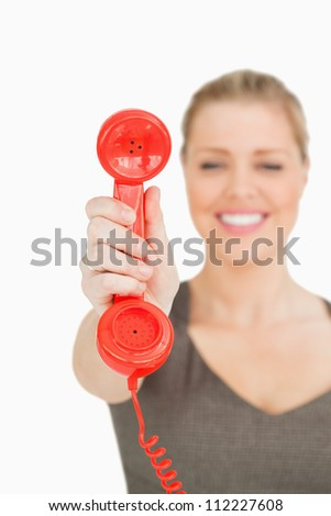 Blurred woman showing a retro phone against white background