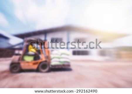 Blurred worker driving a forklift through a warehouse. - stock photo