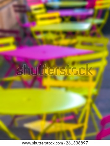 Blurred yellow and pink bistro table and chairs.