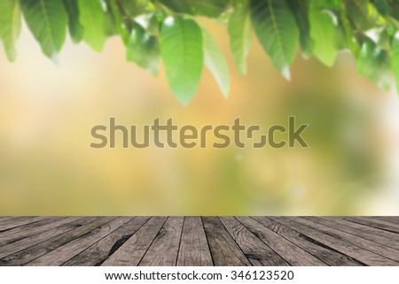 blurred yellow autumn seasonal with blur leaf of tree with wooden tiles plank backdrop:blurry of green backgrounds with bokeh lights:wallpaper with shiny sunny concept:fall and spring conception. - stock photo