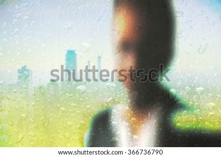 Blurred young businessman working in office behind wet glass. City skyline in the background. - stock photo