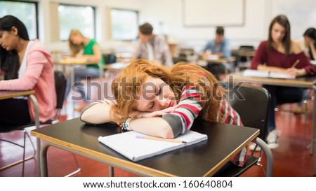 Blurred young college students sitting in the classroom with one asleep girl - stock photo