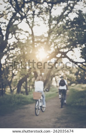 Blurred Young Couple Riding Bicycles Outside with Retro Instagram Style Filter - stock photo
