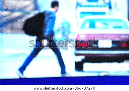 Blurred young man behind wet glass walking at a shopping mall. - stock photo