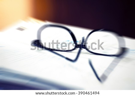 Blurred zoom of Black glasses on the paper report , process in vintage style - stock photo