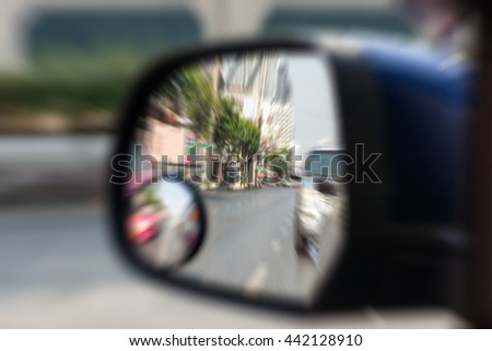 Blurred zoom of Car side mirror for rear view with traffic reflection background - stock photo