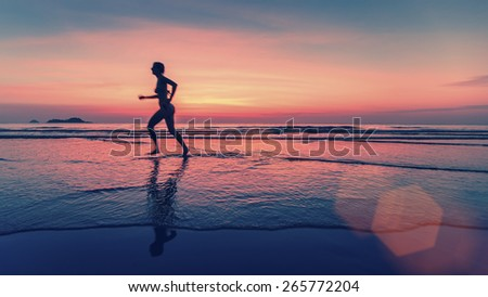 Blurring silhouette of running woman on the sea beach during sunset. - stock photo