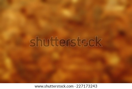 Blurry abstract gold-brownish wallpaper background with texture.
