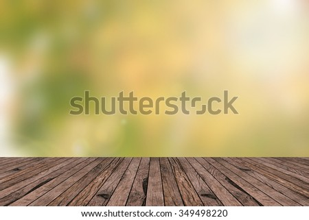 blurry abstract yellow beauty jungle nature in autumn  with wooden panel tiles plank backdrop:blur green sunshine background with lens flare lights:wallpaper sun sunny concept:spring:promotion display - stock photo