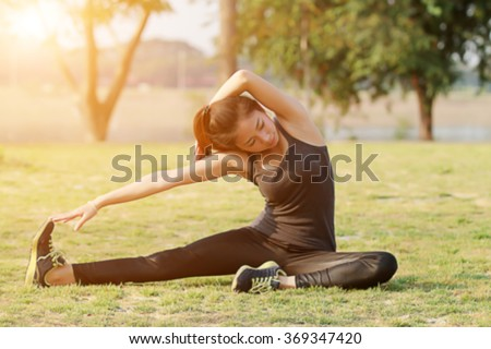 Blurry and soft focus of Athletic woman asian warming up and Young female athlete sitting on an exercising and stretching in a park before Runner outdoor on summer, healthy lifestyle concept - stock photo