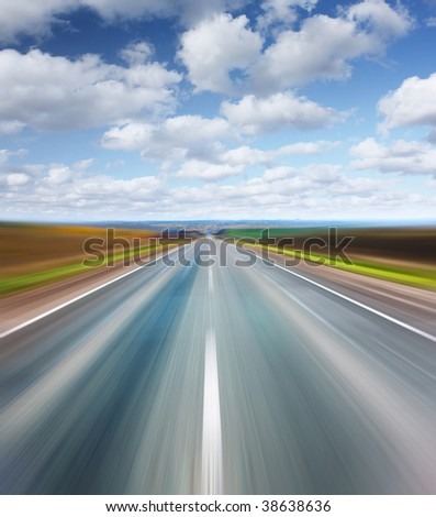 Blurry asphalt road with blue sky and clouds - stock photo