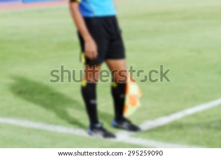 blurry Assistant football referee and Referee's flag - stock photo