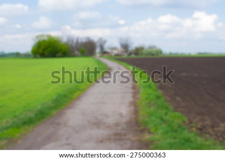 Blurry background - landscape with agricultural fields and country road in central Ukraine
