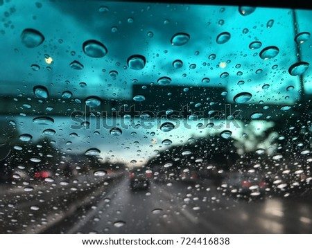 Blurry background, Raindrops on the windshield, street lights at evening on a rainy day.