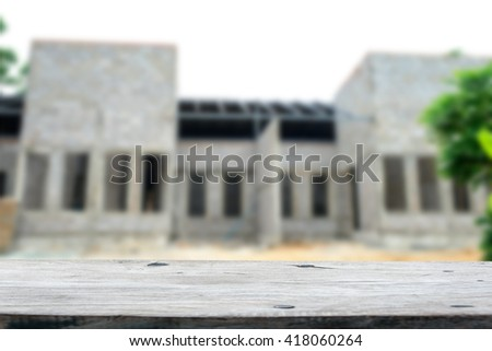 Blurry background Unfinished white brick house with wooden table top - stock photo
