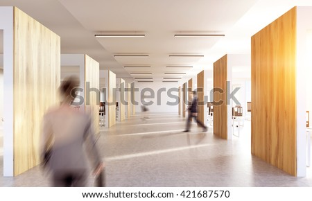 Blurry businesspeople walking in office interior with sunlight - stock photo