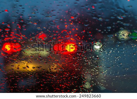 Blurry car silhouette seen through raindrops on the car windshield - stock photo